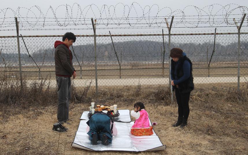 10. Жители Южной Кореи пришли отпраздновать новый год возле колючей проволоки в демилитаризованной зоне Паньмыньчжоне, в Паджу. Это своеобразная дань своим северокорейским предкам.