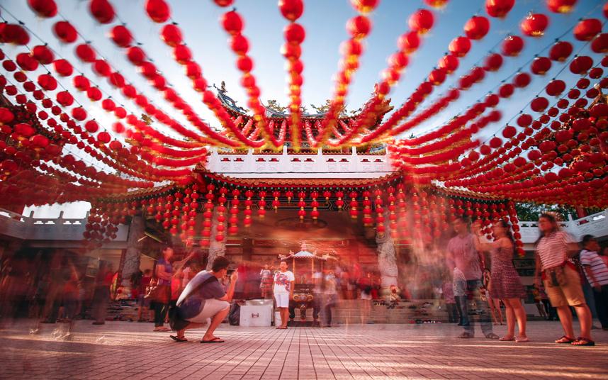 14. Люди фотографируются в украшенном фонариками храме.