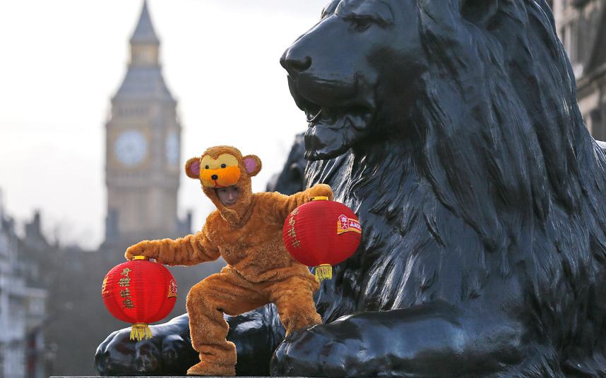 2. Мужчина в костюме обезьяны забрался на одну из статуй львов на Трафальгарской площади в Лондоне.