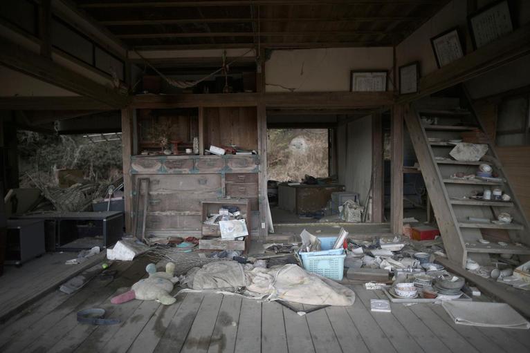 8. Разрушенный цунами дом. Вокруг разбросаны личные вещи жильцов.
