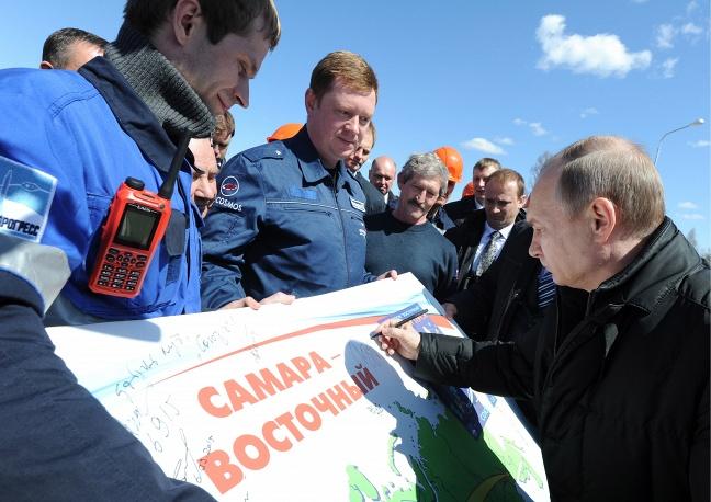 9. Владимир Путин ставит роспись на плакате.
