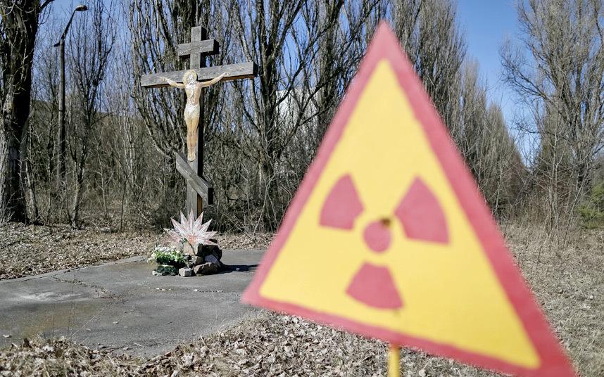 21. Предупреждающий знак об угрозе радиации рядом с распятием.