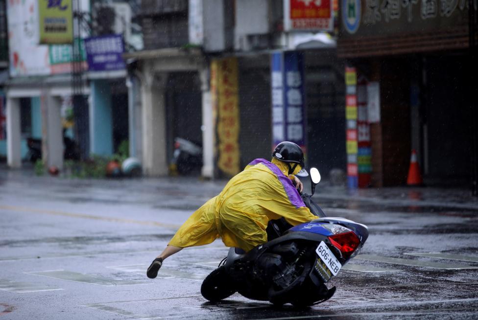 1. Ураганный ветер сбивает водителей скутеров в Тайване в результате тайфуна «Меги».