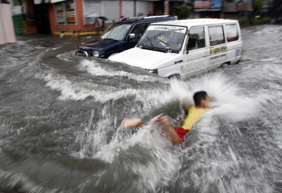 7. Мальчик пытается плыть по затопленной тайфуном Муифа в Маниле улице.