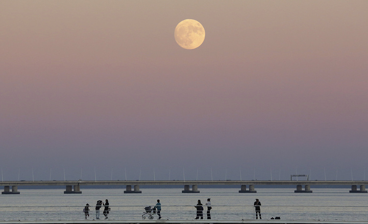 5. Люди прогуливаются вдоль реки Тежу в Лиссабоне, на фоне суперлуния. AP Photo / Армандо Франка.