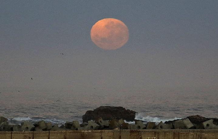 6. Луна поднимается над гаванью города Бей Ламберта, Южная Африка. AP Photo/Schalk van Zuydam.