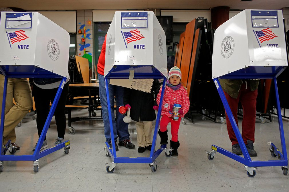 3. Восточный Гарлем, Нью-Йорк. Трехлетняя Мила Гибсон ждет, когда ее отец Кен Гибсон заполнит избирательный бюллетень.