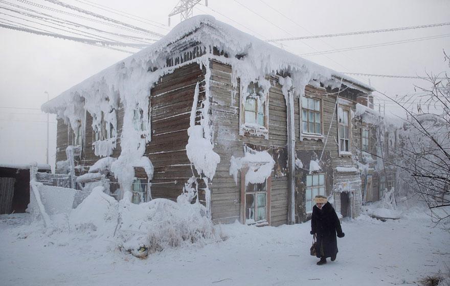 4. Женщина идет мимо замерзшего дома в центре деревни.
