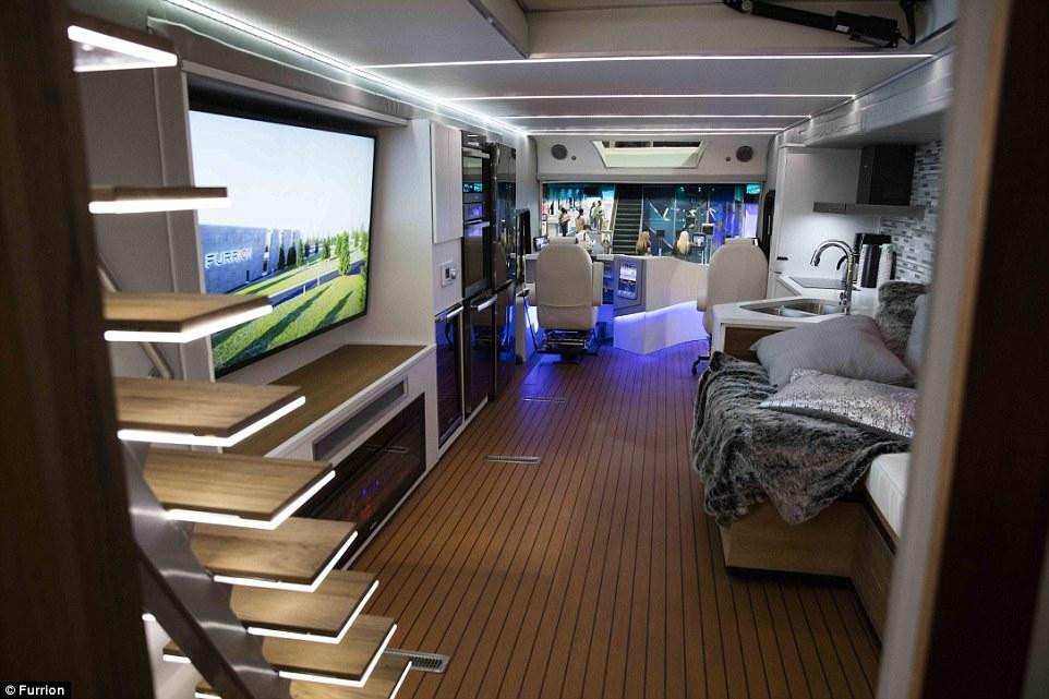5. На фото можно разглядеть водительское кресло. Справа есть раковина и диван, а слева огромный телевизор, холодильник и плита.