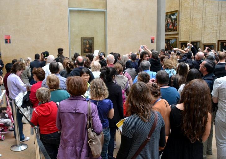 3. Большое количество людей пытаются сфотографировать Мона Лизу.