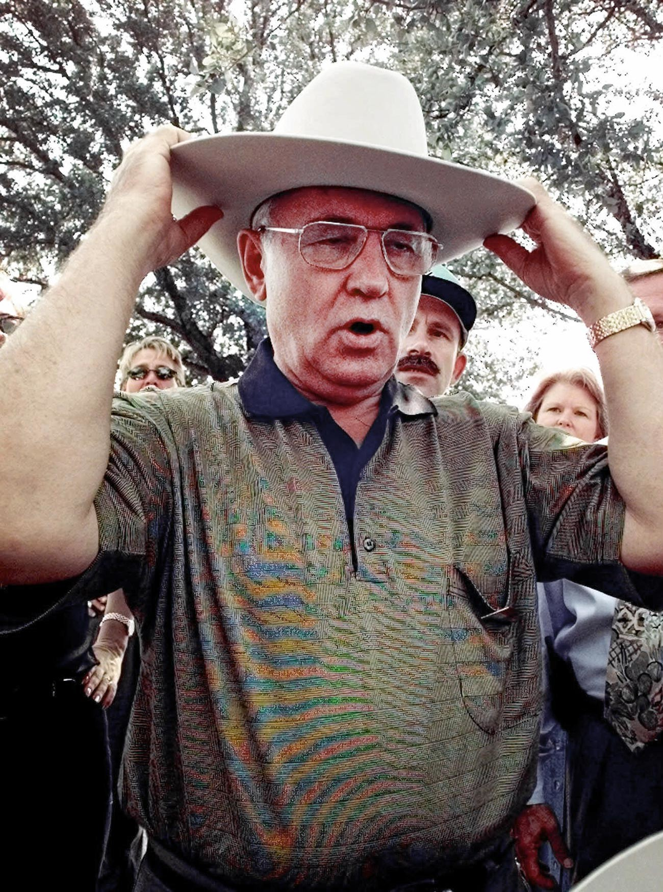 Бывший президент СССР Михаил Горбачев надевает ковбойскую шляпу задом наперед во время посещения ярмарки штата Техас в Далласе, 1998 г.