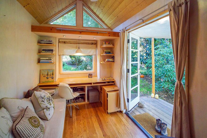 20. Внутри удобный мягкий диван, стол для работы и книжные полки.