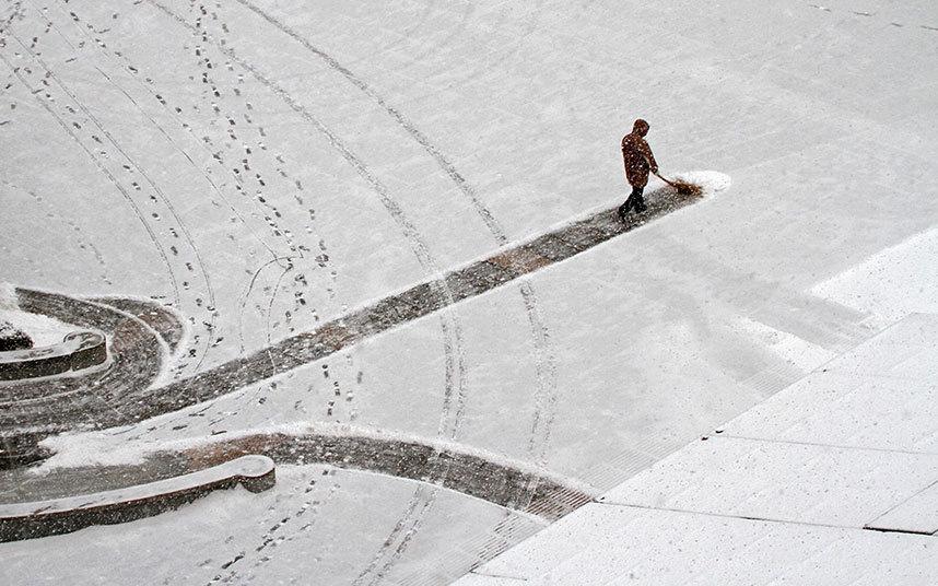 12. Рабочий очищает снег возле больницы в Яньтай, провинция Шаньдун.