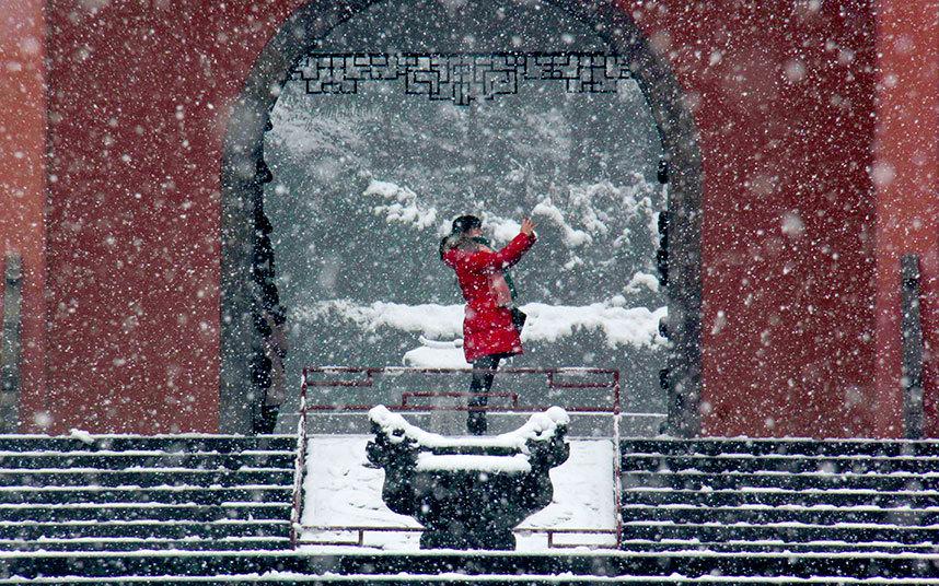 13. Еще Китай. Женщина фотографирует в парке во время метели.
