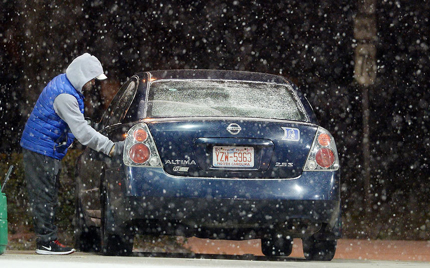 18. Житель Северной Каролины заправляет свой автомобиль газом во время снегопада.