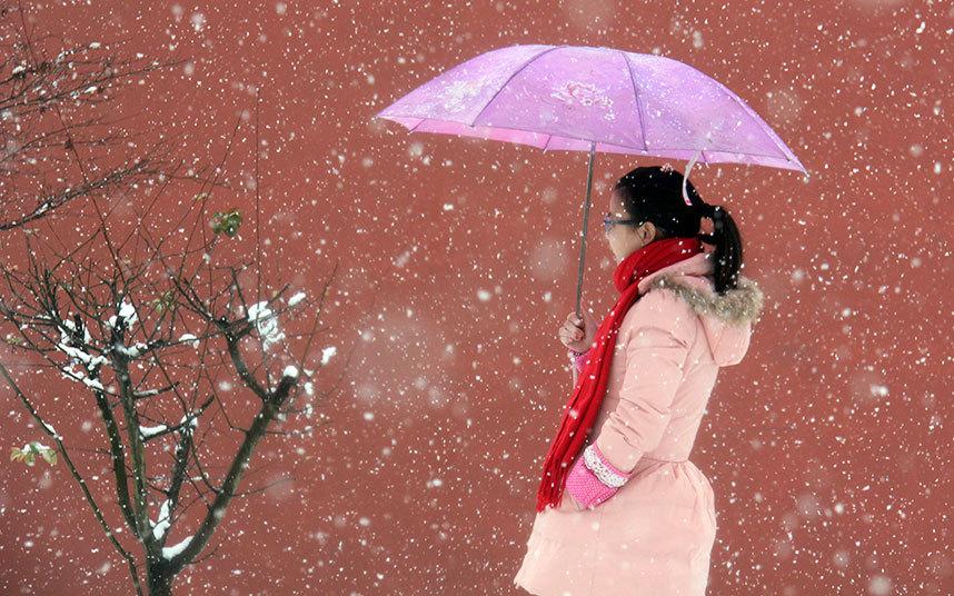 20. Девушка с зонтом во время прогулки в парке в метель. Провинция Чжэцзян Китай.
