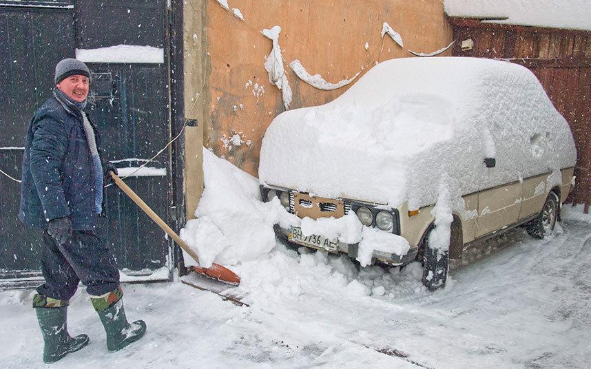 7. Житель Одессы очищает от снега свой автомобиль, после сильнейшего снегопада.