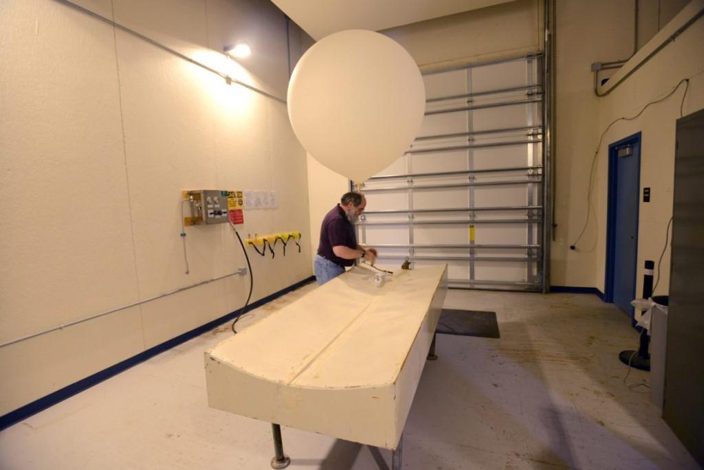 31. Сотрудник метеорологической станции Зигги Бойтор готовит к запуску метеорологический зонд.