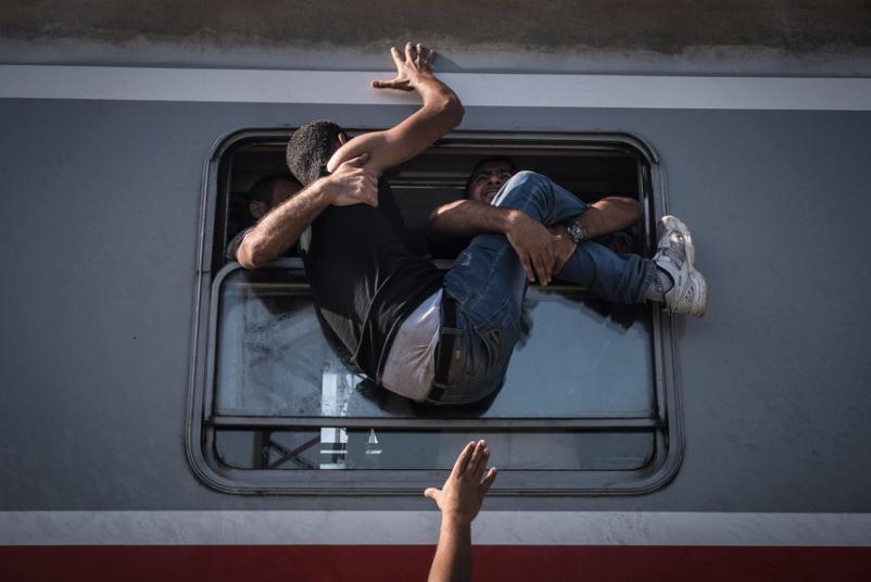 12. Еще одно фото Сергея Пономарева. Беженец пытается попасть на поезд.