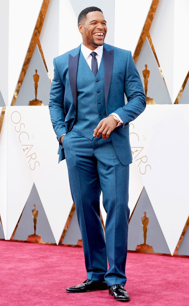 6. Ведущий Майкл Страхан одетый в синий костюм-тройку.