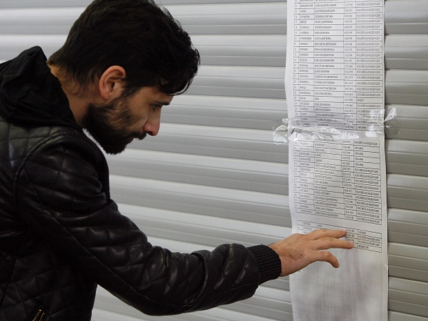 8. Люди ищут в списках погибших имена родных и близких.