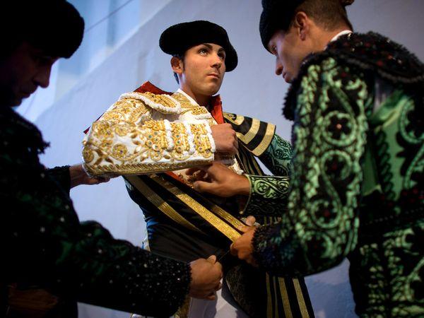 5. Помощники подгоняют одежду испанского матадора Серафина Марина перед боем в Памплоне в 2008 году. Костюм матадора является одной из самых узнаваемых традиционных нарядов Испании.
