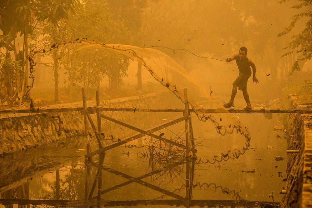 10. Бьорн Ваугн. Рыбак в Индонезии ловит рыбу в загрязненном канале.