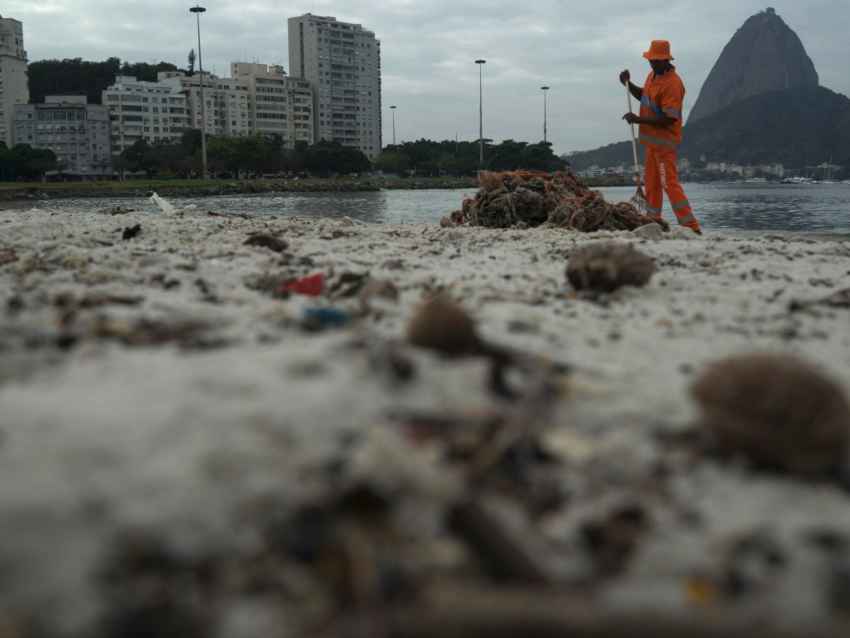 8. В некоторых местах ученые обнаружили опасные бактерии и вирусы уровень которых в 1,7 миллионов раз превышает опасную норму принятую в США. На фото рабочий убирает мусор на пляже Рио Ботафого.