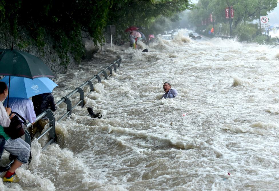 2. Мужчина пытается пробраться через мощный поток воды, вызванный тайфуном Дуджуан в 2015 в Китае.
