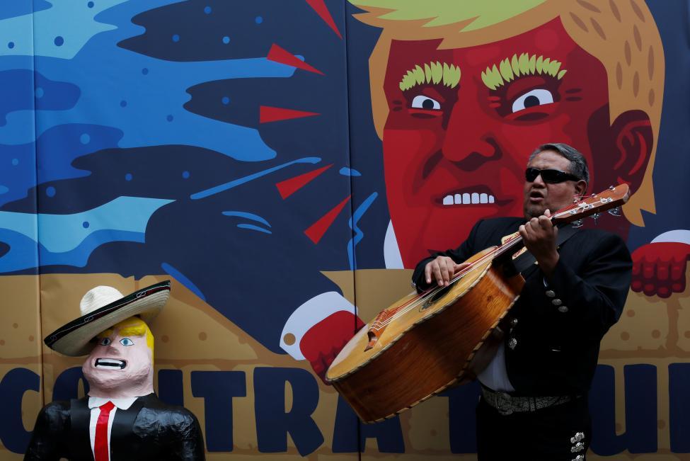8. Член мариачи играет рядом с пинатой (мексиканская игрушка из папье-маше) и стеной с каррикатурой на Трампа, агитирующей голосовать против кандидата. Мехико, Мексика. REUTERS / Карлос Джассо